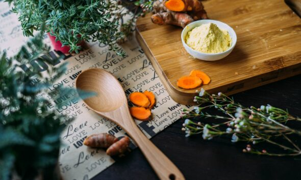 Ground turmeric in a bowl on a wooden chopping board, with slices of fresh turmeric and plants