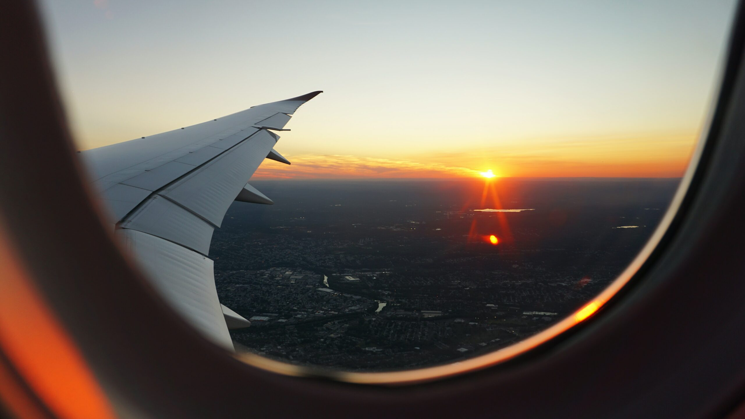 Looking out of an airplane window over the wing tip at a sunrise