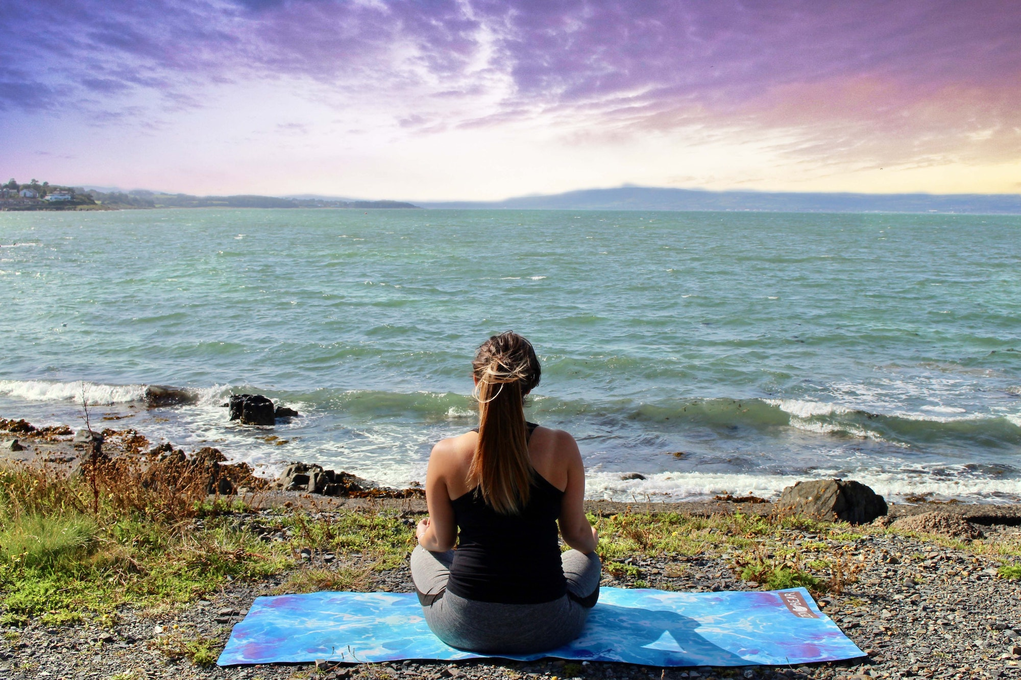 Woman sitting on a blue yoga mat looking out to sea