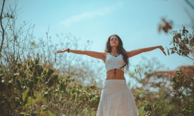 Girl in white top and skirt with arms outstretched with trees and sky in the background