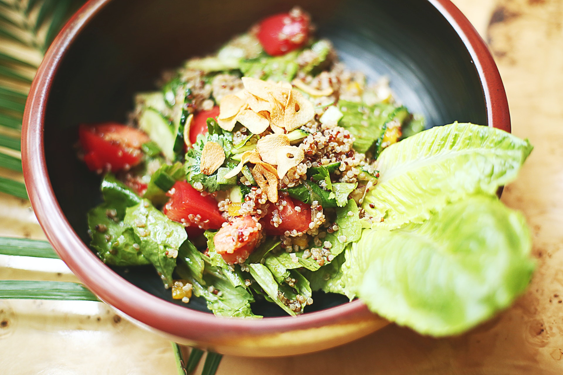 Superfood salad in a green and brown bowl