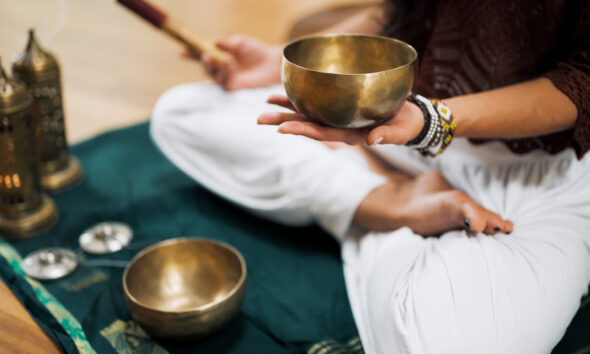 A man sitting in a meditation posture holding a bronze bowl