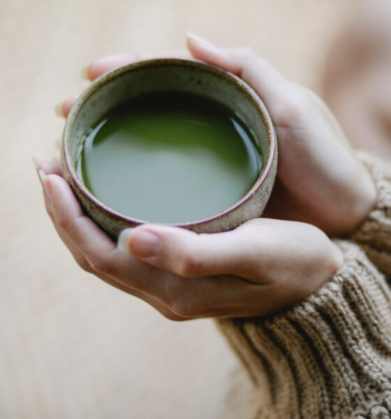 Hands holding green juice cup