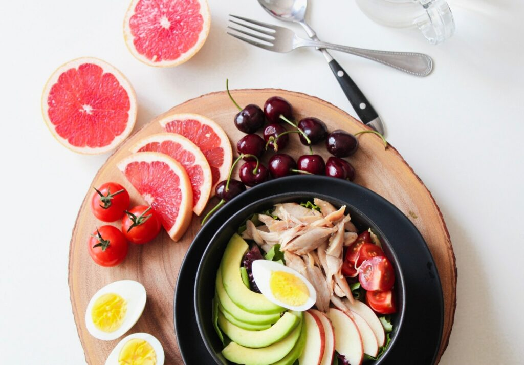 a variety of healthy foods and vegetables on a wooden plate